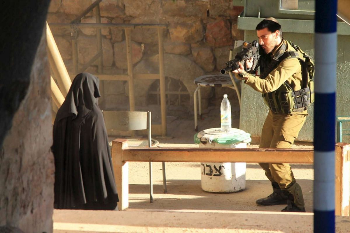 An Israeli soldier aims his rifle at a woman said to be 19-year-old Palestinian student Hadeel al-Hashlamun, before she was shot and killed by Israeli troops, at an Israeli checkpoint in the occupied West Bank city of Hebron on September 22, 2015. Th