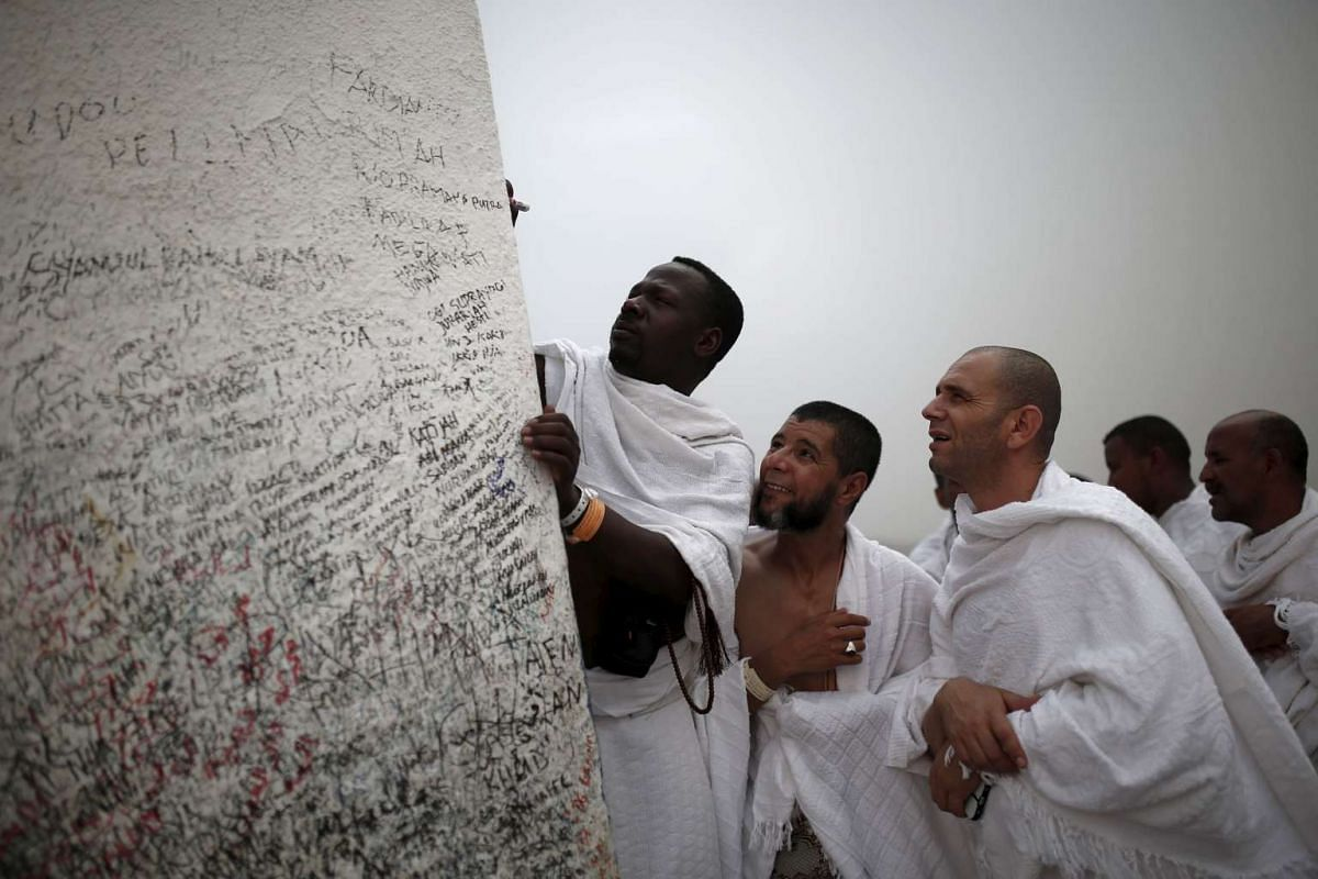 Muslim pilgrims touching a rock atop Mount Mercy on the plains of Arafat during the annual haj pilgrimage, outside the holy city of Mecca on Sept 22, 2015.