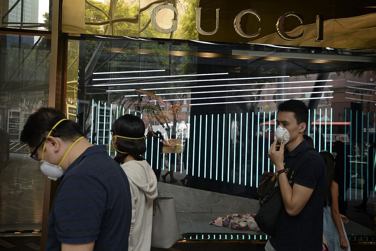 1.30pm: People wearing masks pass by a Gucci shop along Orchard Road.
