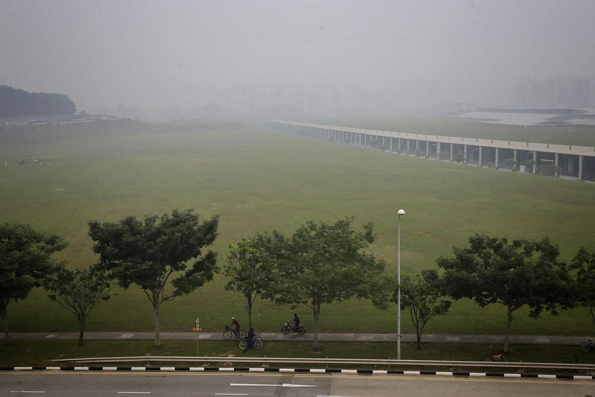 9.20am: A cyclist travels along Sengkang East Road with HDB blocks on the horizon barely visible in hazy conditions.