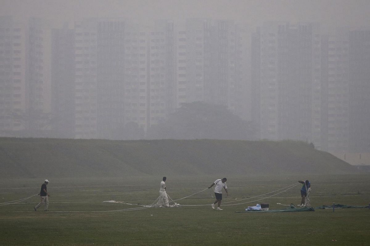 8.30am: A group of men carrying out activities on an open field along Sengkang East Road in hazy conditions.