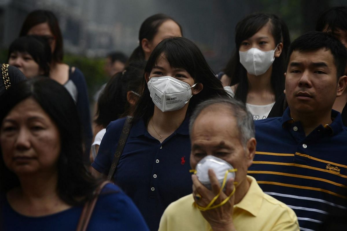 1pm: People wearing masks cross a traffic junction along Orchard Road.