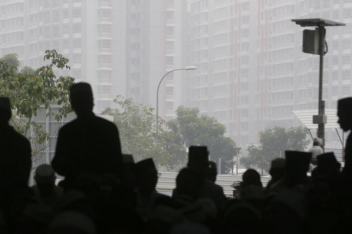 7.45am: Mosque congregants silhouetted against a hazy backdrop outside Al-Mawaddah Mosque.