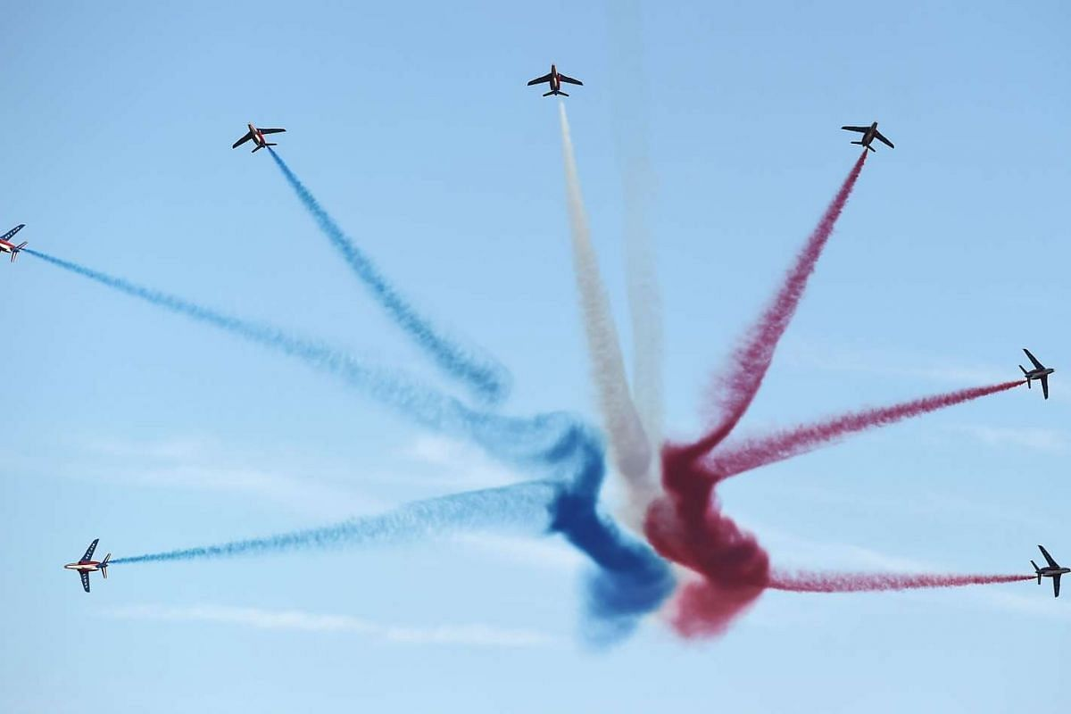 "Alphajet aircrafts from the French elite acrobatic flying team ""Patrouille de France"" (PAF) release smoke in the colors of the French national flag on September 24, 2015, during a training session in Haguenau, eastern France, ahead of an airshow meet"