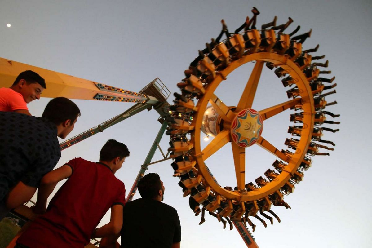 Iraqis ride a ferris wheel at an amusement park in the southern city of Basra on the first day of the Muslim Eid al-Adha (Feast of the Sacrifice) holiday on September 24, 2015.