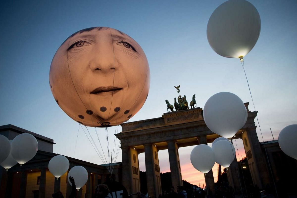 A giant balloon featuring the face of German chancellor Angela Merkel floats amid smaller white balloons in front of the Brandenburg Gate, a major landmark of Berlin, Germany, 24 September 2015. The advocacy organisation 'ONECampaign' is hosting t