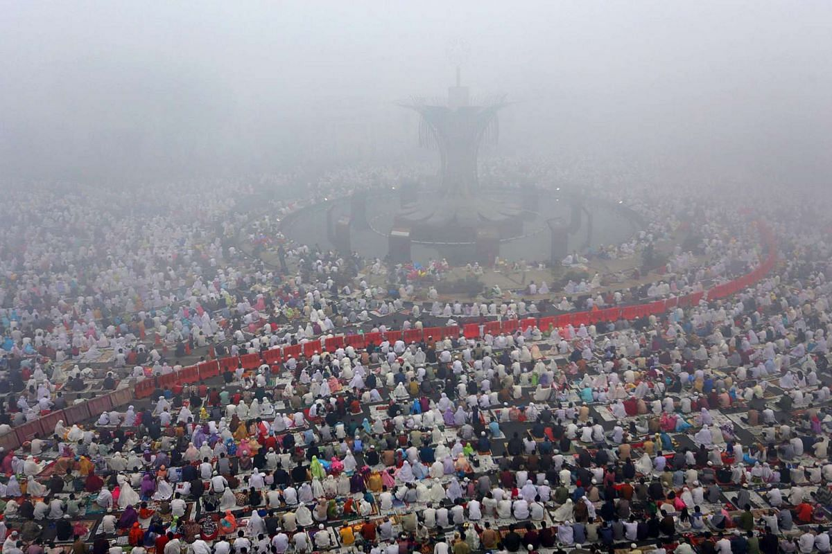 Muslim people attend an Eid al-Adha mass prayer as haze shrouds at Agung Mosque in Palembang on Indonesia Sumatra island on September 24, 2015 in this picture taken by Antara Foto. Indonesia has ordered four companies to suspend operations for allege