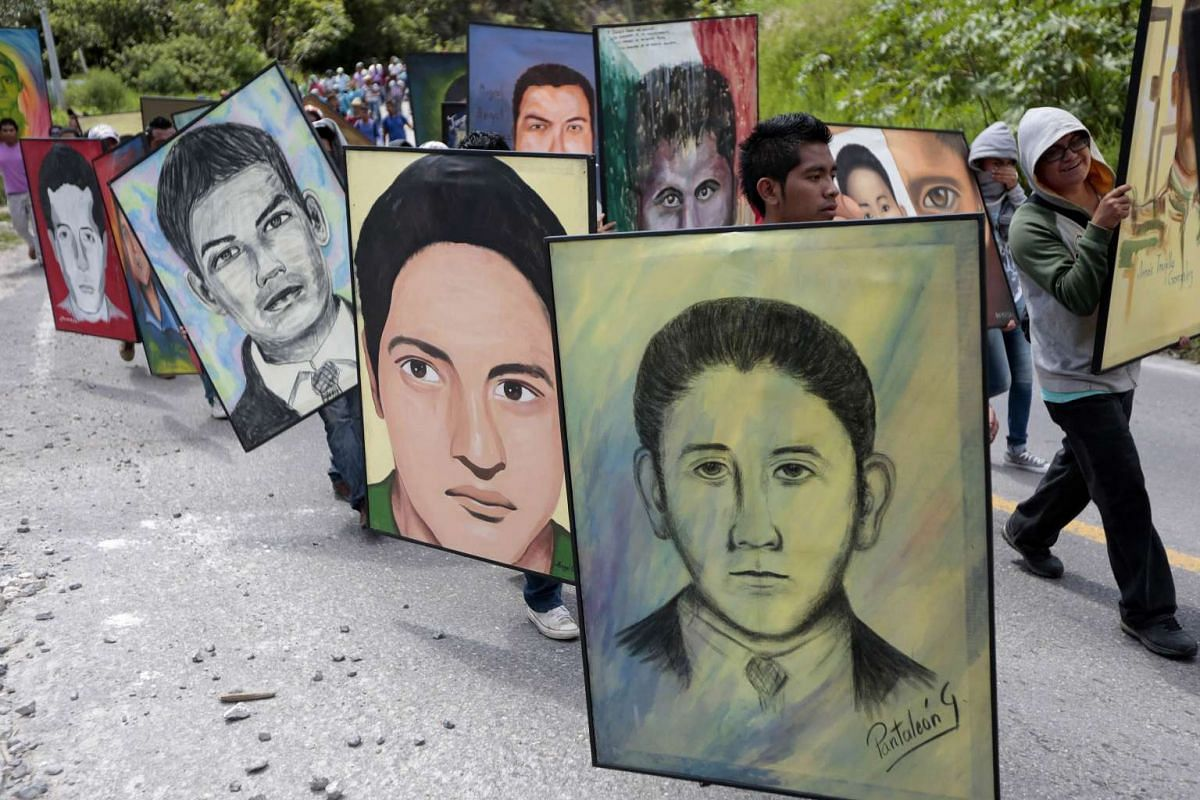 Students of  the rural teacher college of Ayotzinapa hold portraits of the 43 missing students during a march from the school to Chilpancingo, Guerrero State, Mexico, on September 24, 2015. Next September 26 will mark the first anniversary of the mas