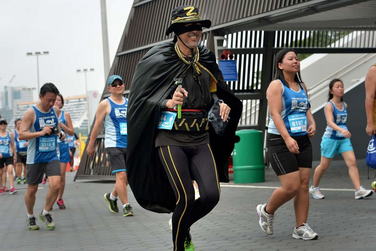 Francis Chia, 53, dressed up as the masked character Zorro as he takes part in the 5km race.