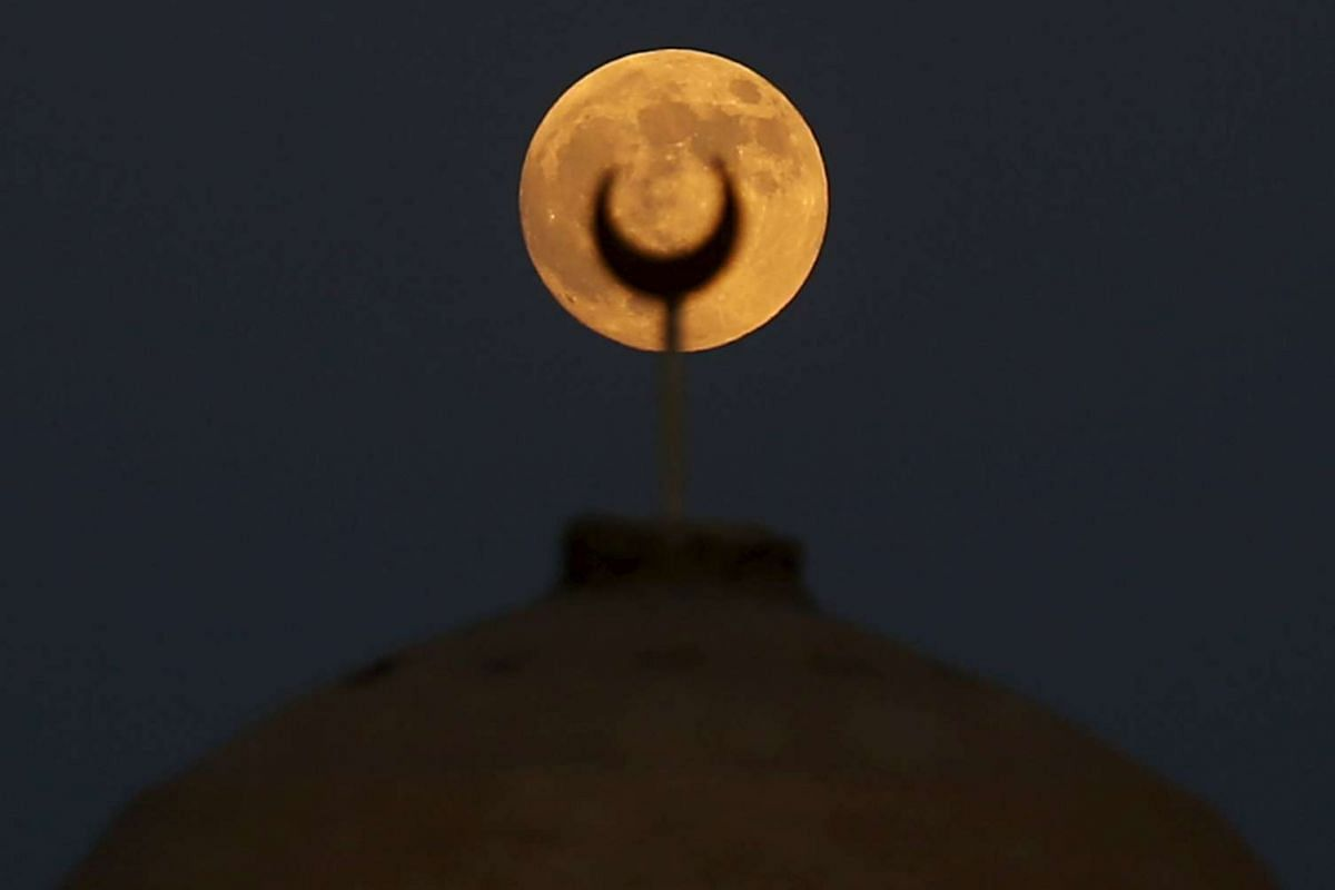 A supermoon, the last of this year's supermoons, rising over a minaret of a mosque in Wadi El-Rayan Lake at the desert of Al Fayoum Governorate, south-west of Cairo on Sept 27, 2015.