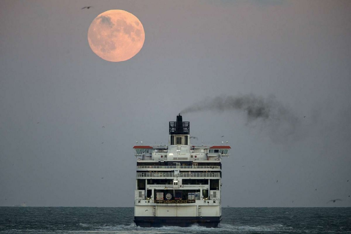 The moon seen above a cross channel ferry leaving the port of Dover in southern England on Sept 27, 2015.
