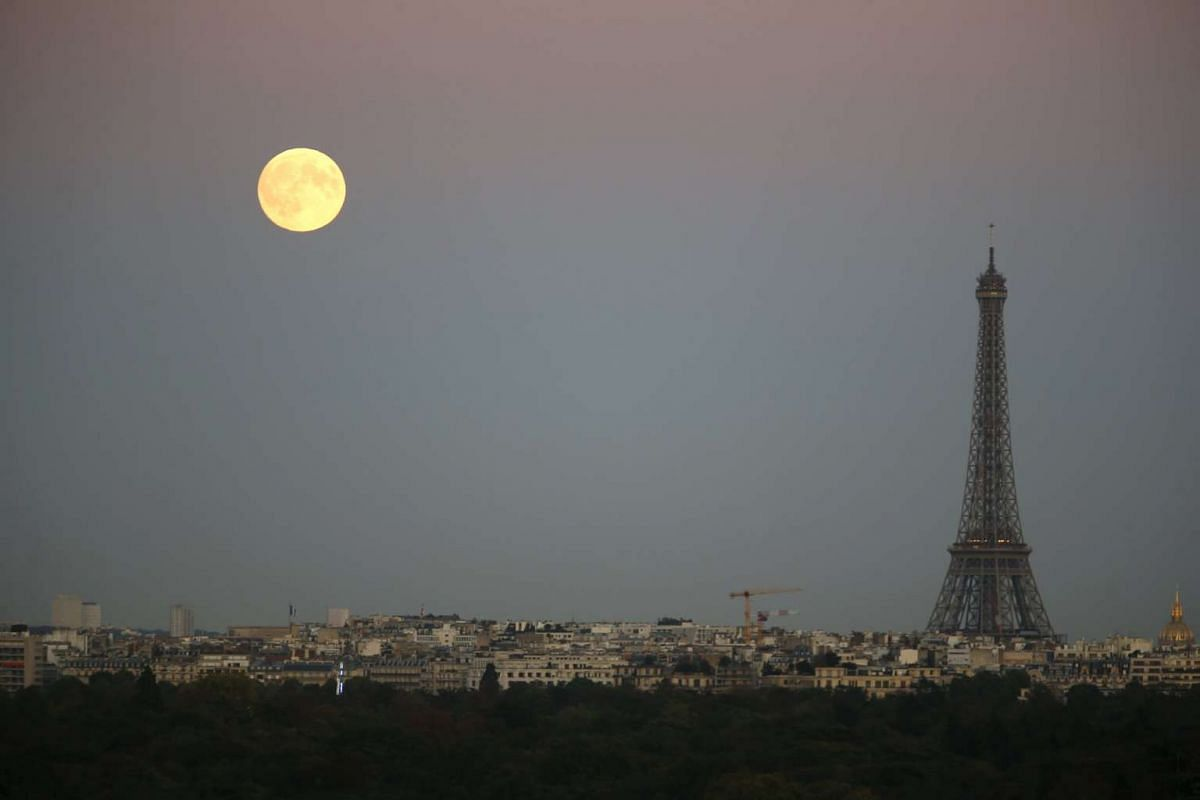 A supermoon rises in the sky near the Eiffel Tower as seen from Suresnes, western Paris, on Sept 27, 2015.