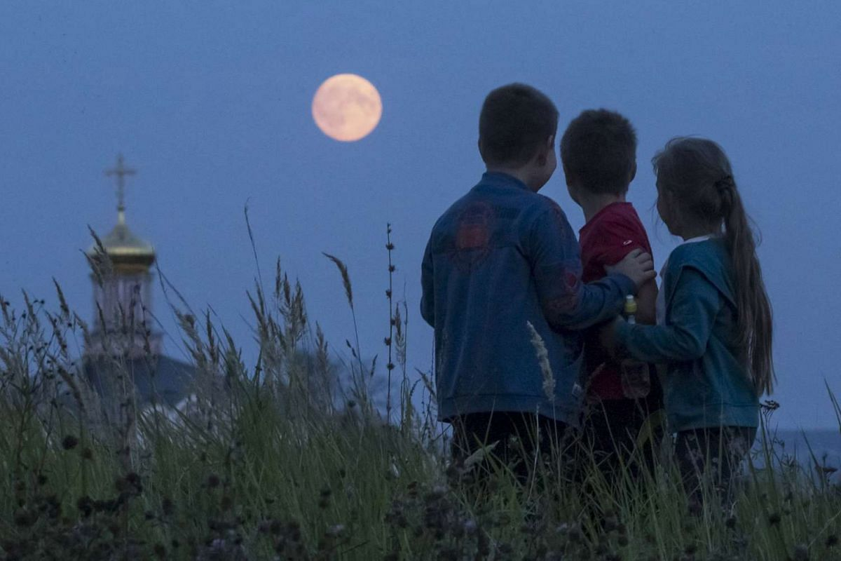 Children looking at the moon in the settlement of Poschupovo in Russia's Ryazan region on Sept 27, 2015.