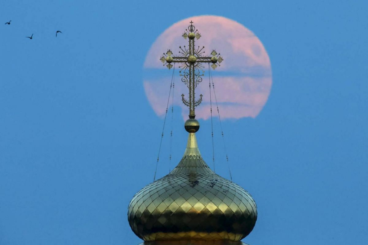 A cross atop a local monastery in front of the moon in the settlement of Poschupovo in the Ryazan region of Russia on Sept 27, 2015.