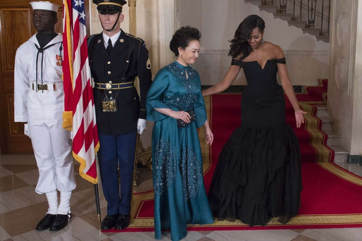 Chinese First Lady Peng Liyuan (left) being escorted by US First Lady Michelle Obama.