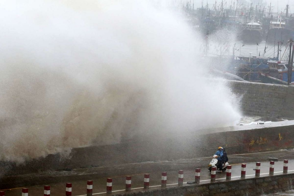 A huge wave crashes over a wall as two people ride on a scooter over a pier in Hui'an county in Quanzhou, east China's Fujian province on Sept 29, 2015. Super typhoon Dujuan has killed three people and left more than 300 injured in Taiwan.