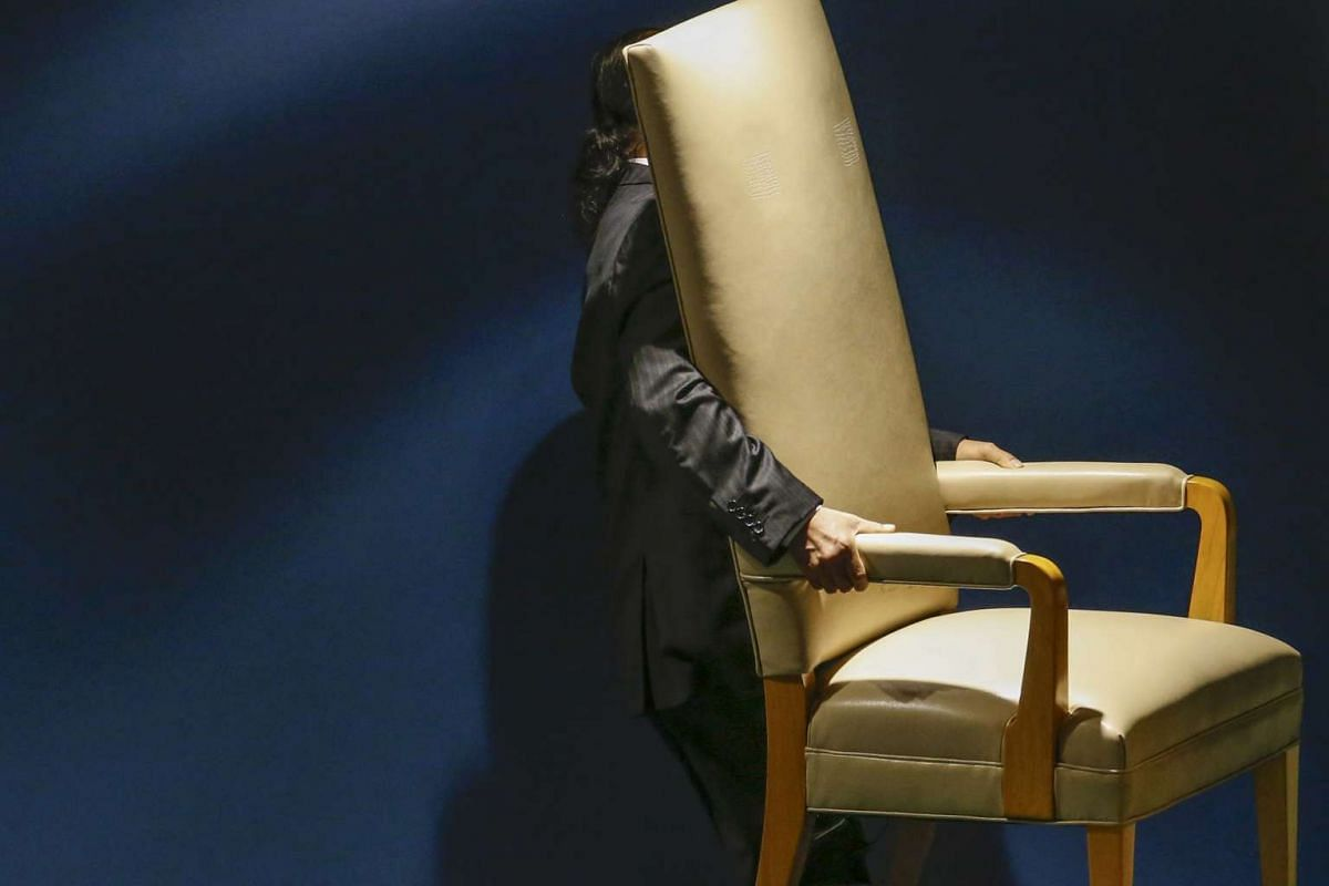 A man carries out the chair reserved for the head of states that will be used before they address attendees during the 70th session of the United Nations General Assembly at the U.N. Headquarters in New York, Sept 29, 2015.