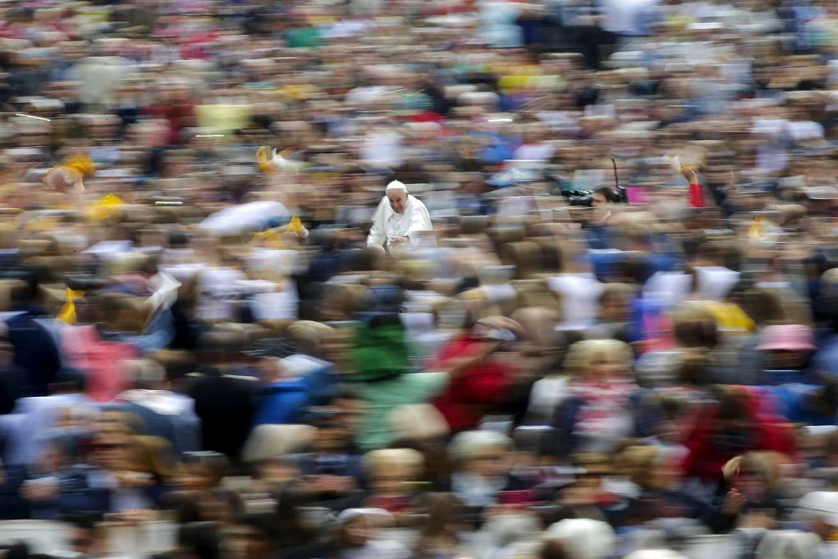Pope Francis blessing the faithful as he leads the weekly audience in Saint Peter's square at the Vatican on Sept 30, 2015.