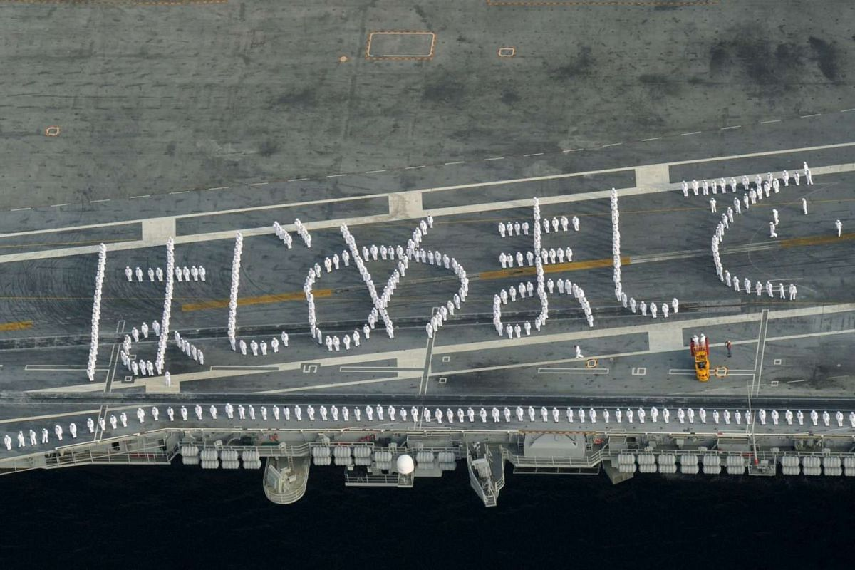"""US sailors on the deck of the USS Ronald Reagan, a Nimitz-class nuclear-powered super carrier, forming words in Japanese which mean loosely in English """"Nice to meet you"""" upon the carrier as it arrives at the US naval base in Yokosuka, south of Tokyo,"""