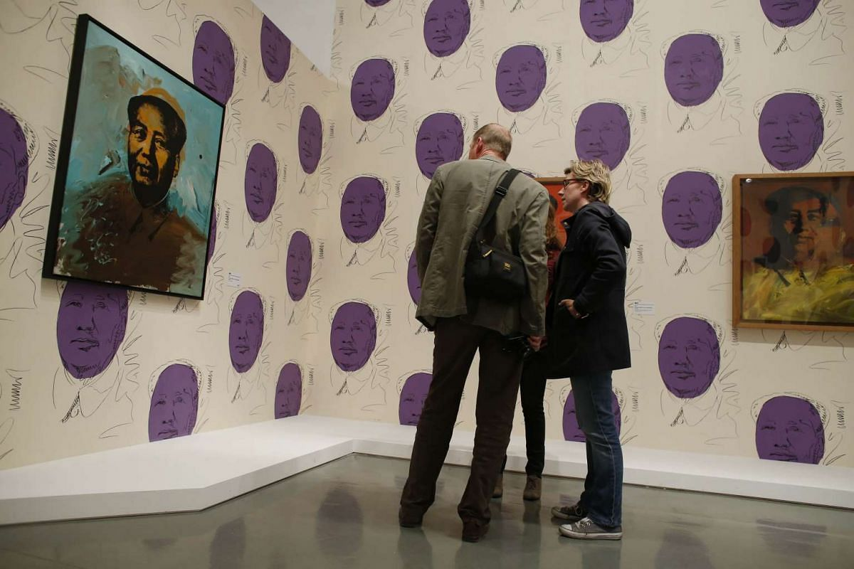 People looking at a painting by the late American artist Andy Warhol entitled Mao on the opening day of the exhibition Warhol Unlimited at the Musee d'Art Moderne de Paris, in Paris, on Oct 1, 2015.