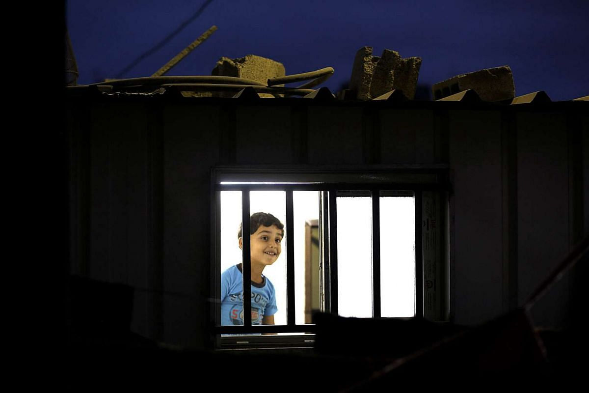 Six-year-old Mohammed Al Za-aneen looking from the window of his family's temporary housing next to their house which was damaged during the Israeli war against Gaza in 2014, in the east of Beit Hanun town in the northern Gaza Strip. More than 100,00