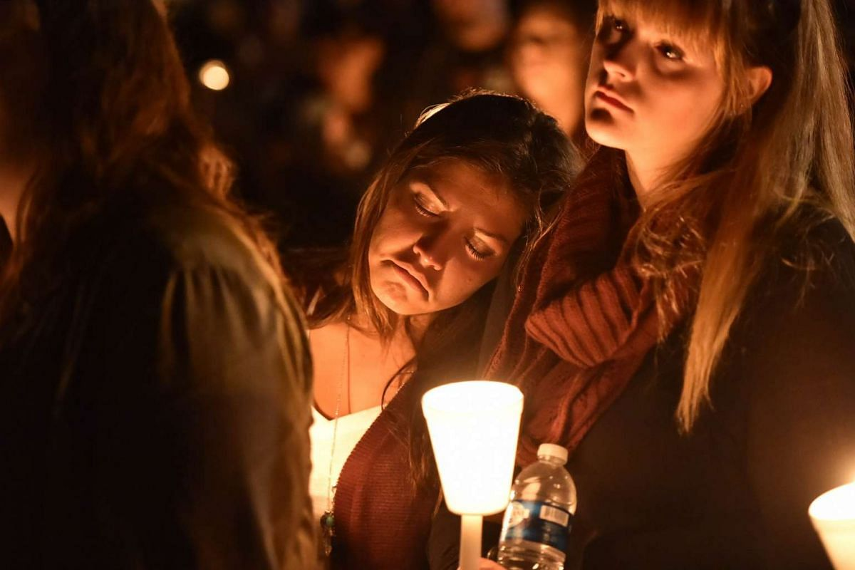 Kristin Sterner (centre), a freshman at Umpqua Community College, at a vigil in Roseburg, Oregon, on Oct 1, 2015, for the 10 people killed and seven others wounded in a shooting at a community college in the western US state. The 26-year-old gunman,