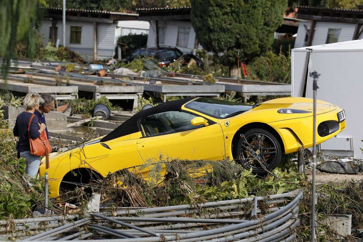People looking at a car destroyed during the floods in Biot, southern France, on Oct 4, 2015.
