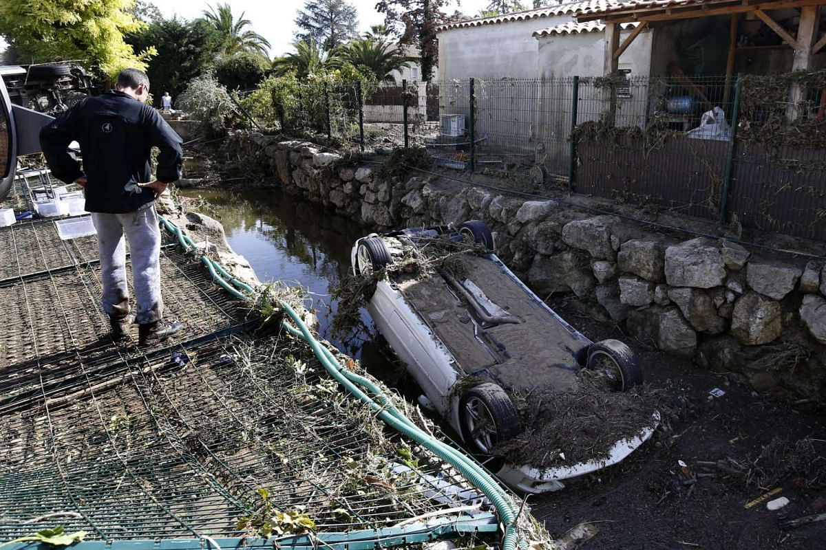 A man looking at a vehicle destroyed during the floods in Biot, southern France, on Oct 4, 2015.