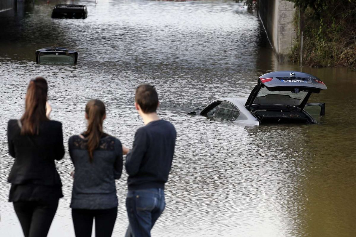 People looking at vehicles destroyed by floods in Mandelieu la Napoule in southern France on Oct 4, 2015.