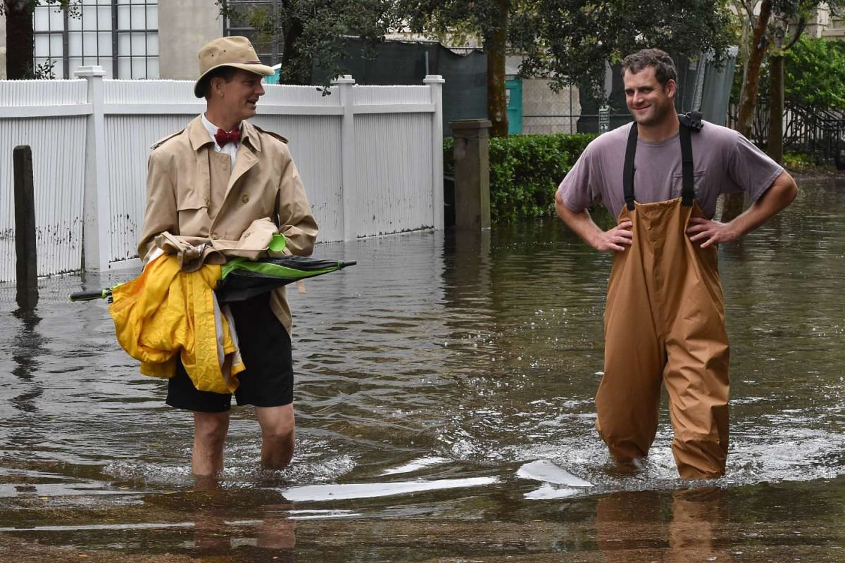 Two men wading through a flooded street in downtown Charleston, South Carolina, on Oct 4, 2015.