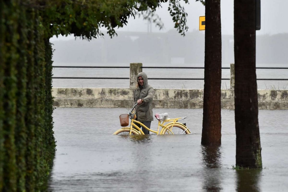 A woman pushing her bicycle on a flooded street in downtown Charleston, South Carolina, on Oct 4, 2015.