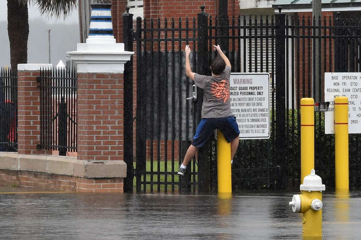 A boy trying to stay dry by climbing along a fence on a flooded street in Charleston, South Carolina, on Oct 4, 2015.