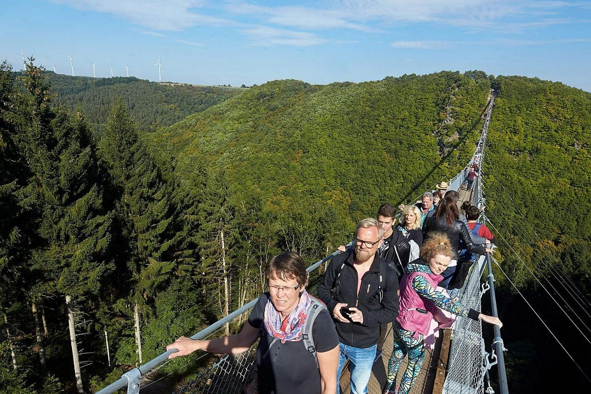 The first tourists taking in the dizzying views crossing the Geierlay rope suspension bridge above the Geierley canyon between Moersdorf and Sosberg, Germany, on Oct 3, 2015.