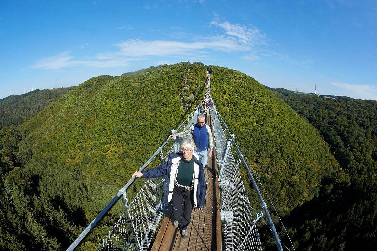 Fearless tourists crossing the newly erected Geierlay rope suspension bridge while soaking in the stunning scenery.