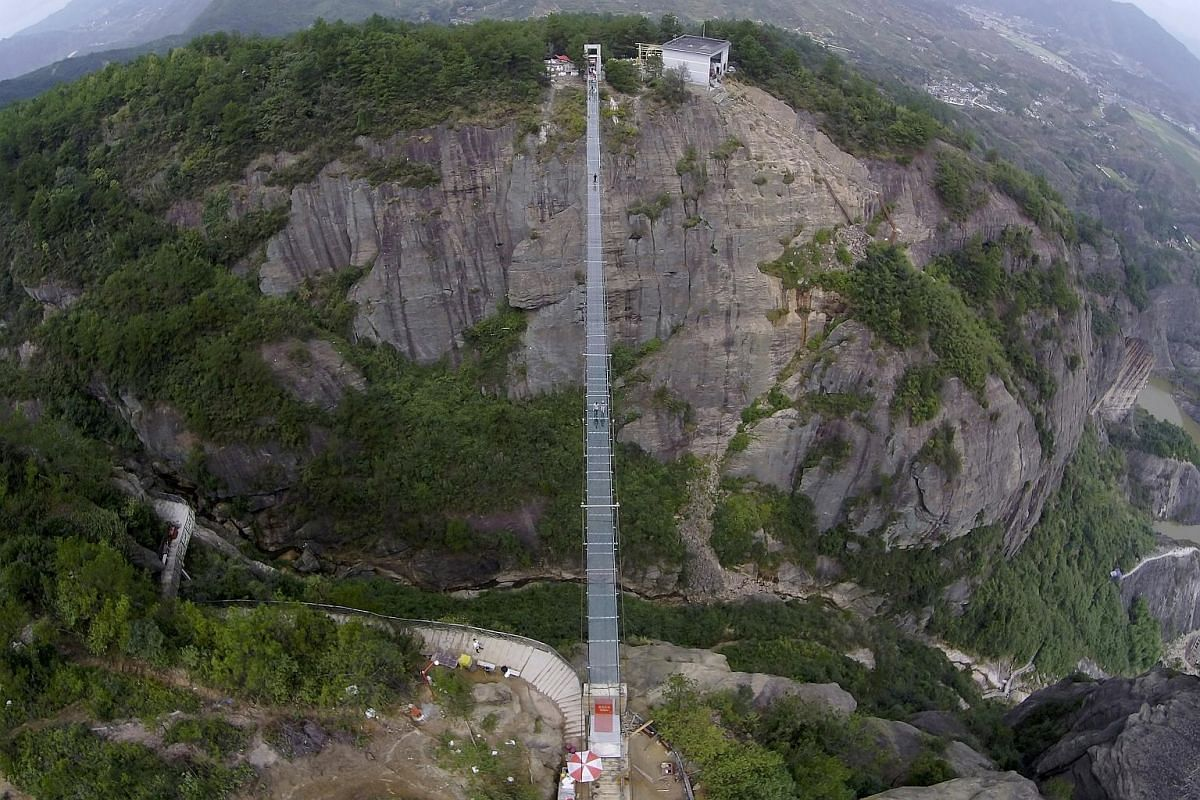 Float right above the valley crossing the glass suspension bridge at the Shiniuzhai National Geo-park in Pinging county in Hunan province, China. Opened on Sept 24, 2015, it spans 300m long and is suspended 180m above the valley floor.