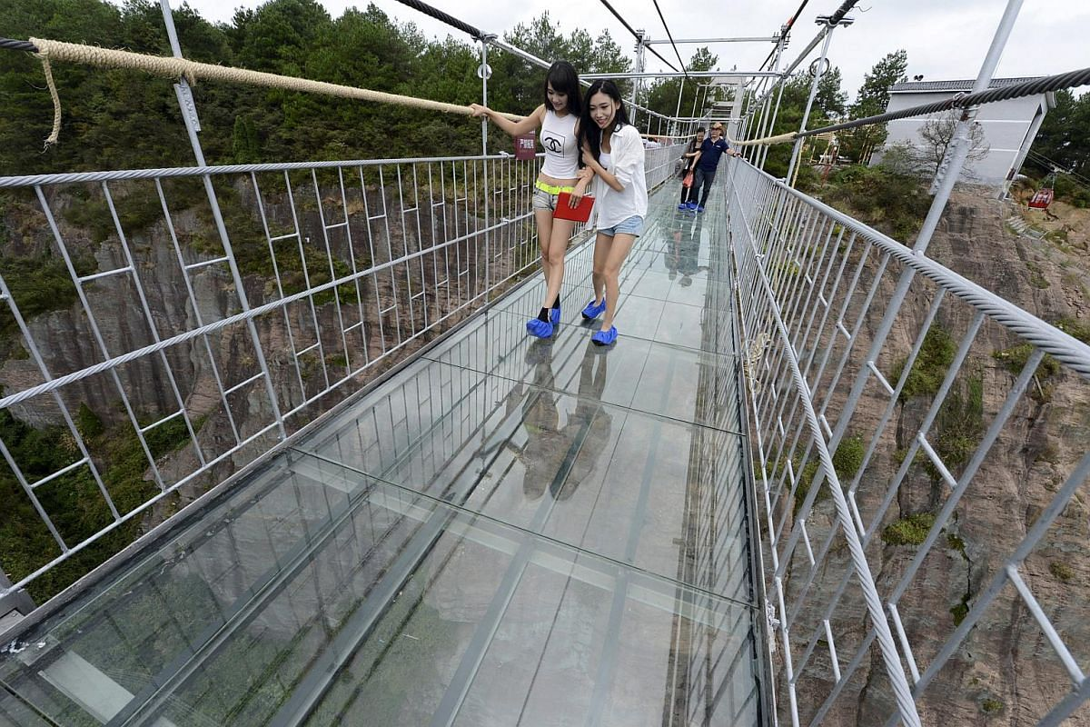 Daring yet faint-hearted tourists looking down as they walk across the glass suspension bridge at the Shiniuzhai National Geo-park in Pinging county in Hunan province, China.