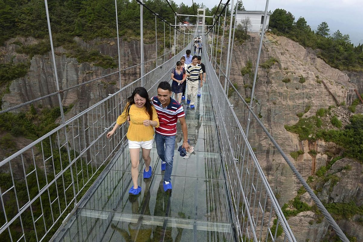 A heart-in-the-mouth walk for the tourist as she walks - with much encouragement - across the glass suspension bridge at the Shiniuzhai National Geo-park in Pinging county in Hunan province, China.