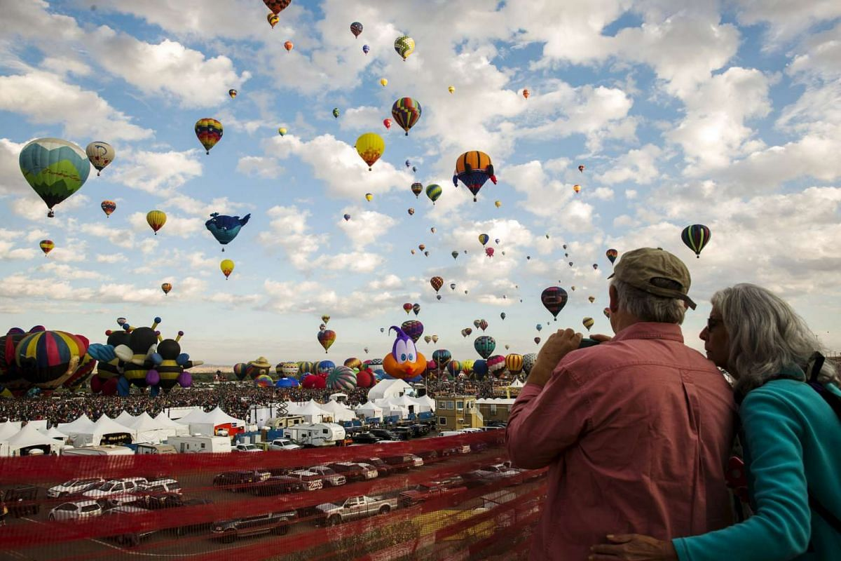 Attendees watch as hundreds of hot air balloons lift off on the first day of the 2015 Albuquerque International Balloon Fiesta in Albuquerque, New Mexico, Oct 3, 2015.