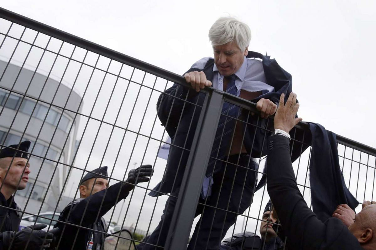 Director of Air France in Orly Pierre Plissonnier, nearly shirtless, tries to cross a fence, helped by security and police officers, after several hundred of employees invaded the offices of Air France, interrupting the meeting of the Central Committ