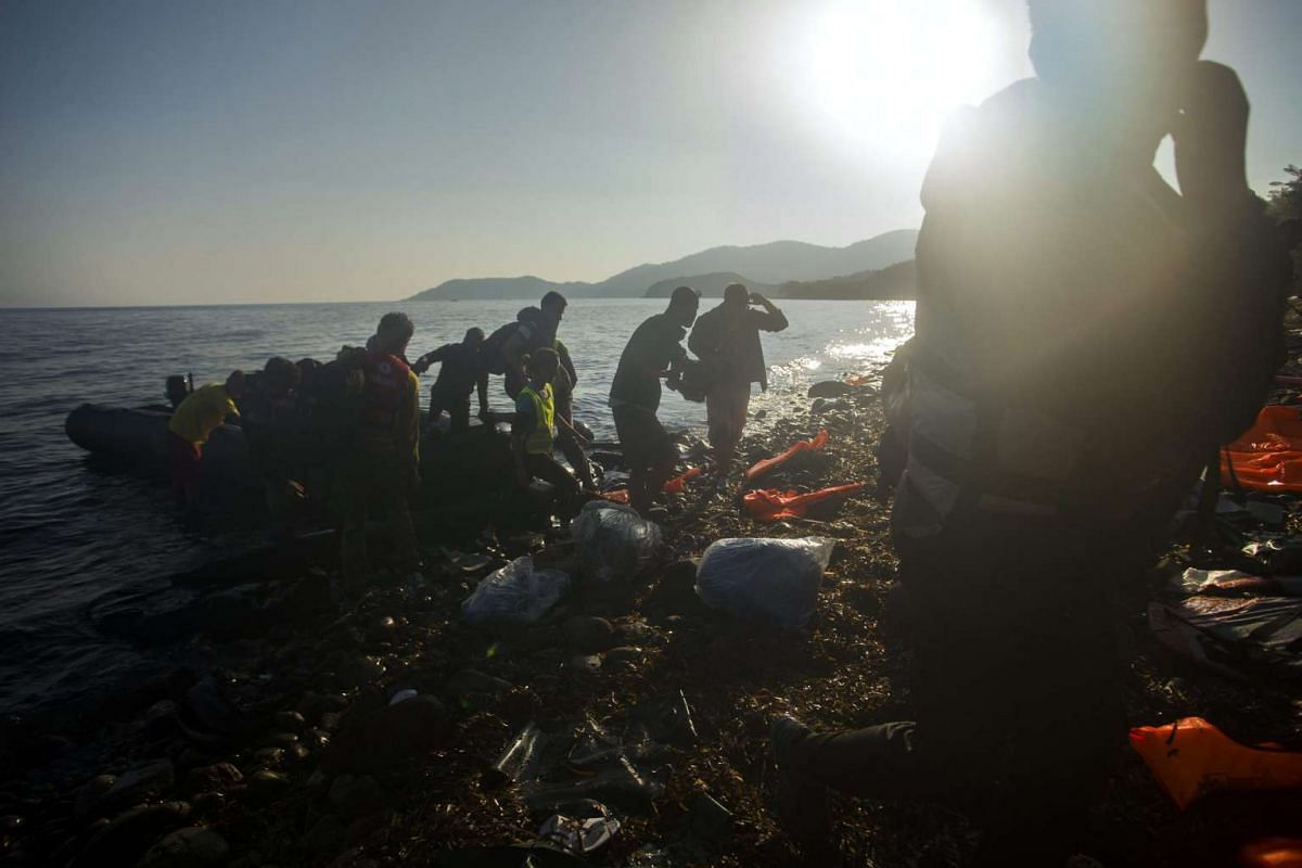 Migrants, who came across Turkey, make land from an overloaded rubber dinghy as they arrive at the coast near Mithimna, Lesbos island, Greece, 5 Oct 2015.