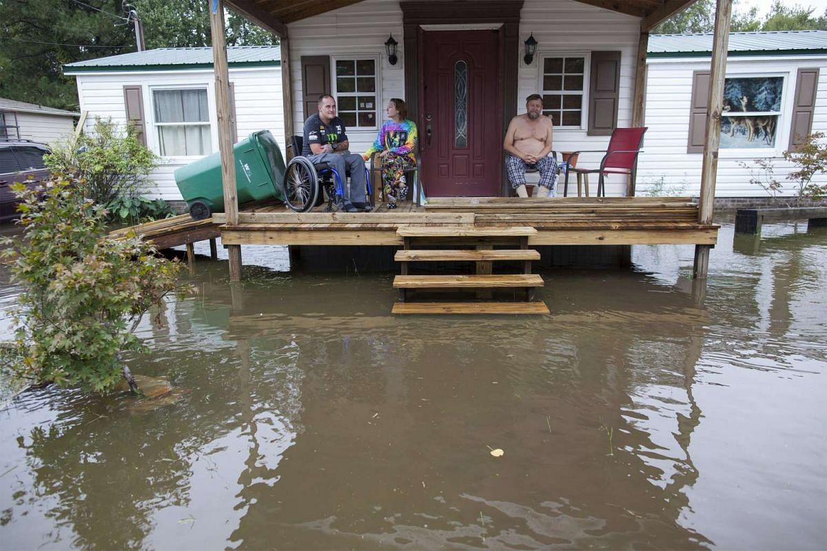 Chris Stumbo (L-R), his girlfriend Felicia Howerton and Paul Stumbo check out the level of flood waters surrounding their home on Applewood Court in Myrtle Beach, South Carolina Oct 5, 2015.