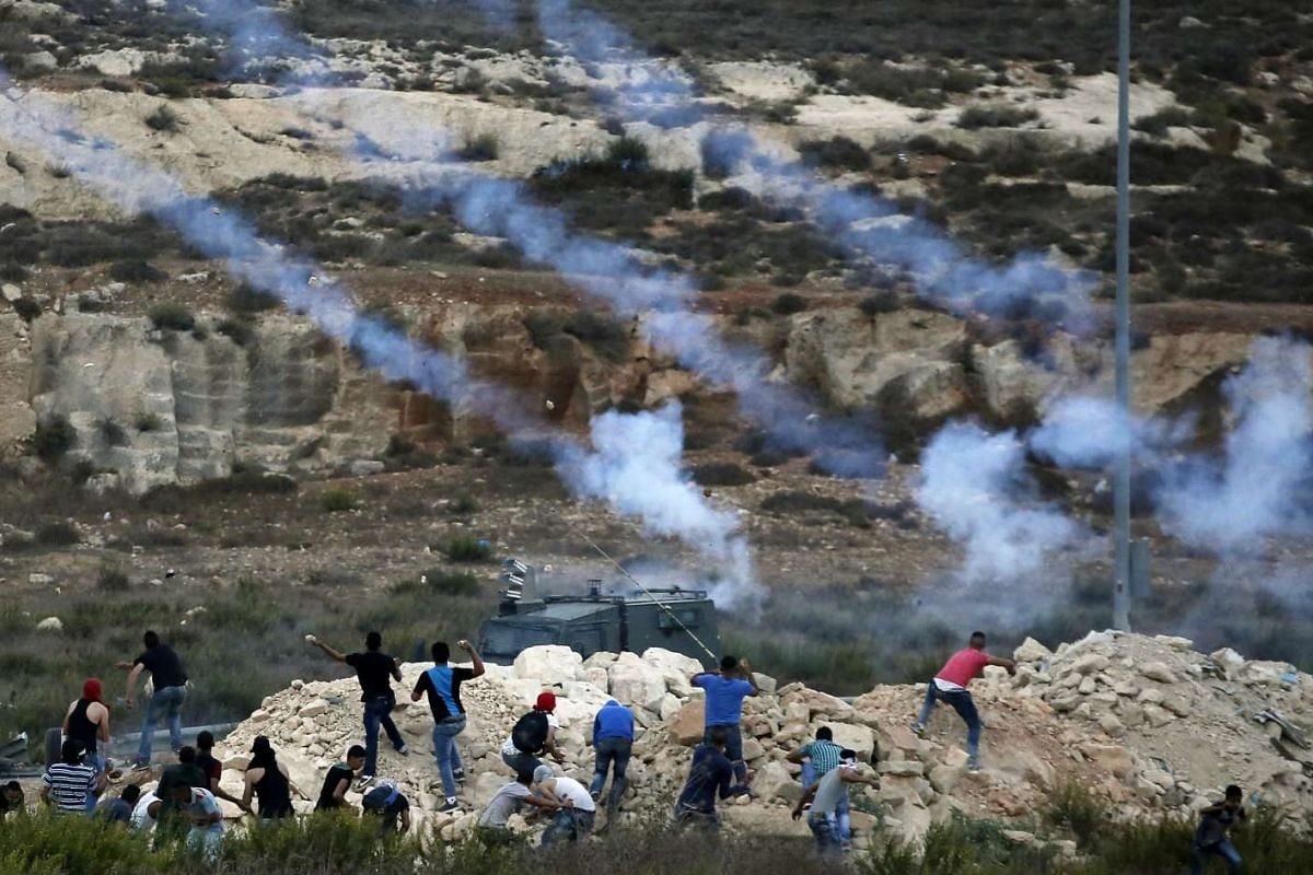 Israeli security forces fire tear gas towards Palestinian students throwing stones during clashes near the Jewish West Bank settlement Beit El, north of Ramallah on Oct 5, 2015 as violence spiked in east Jerusalem and the occupied West Bank.