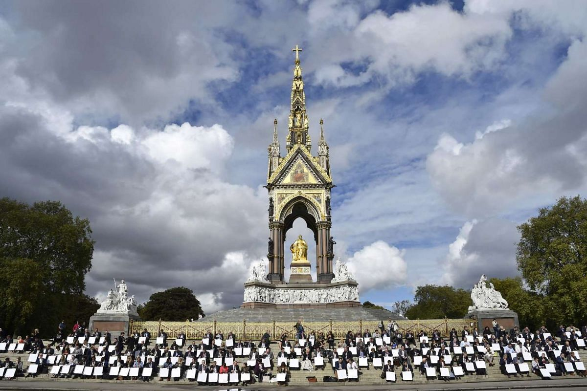 Business delegates eat lunch from picnic boxes on the steps of the Albert Memorial statue during the Institute of Directors convention at the Royal Albert Hall in London, Britain, Oct 6, 2015.
