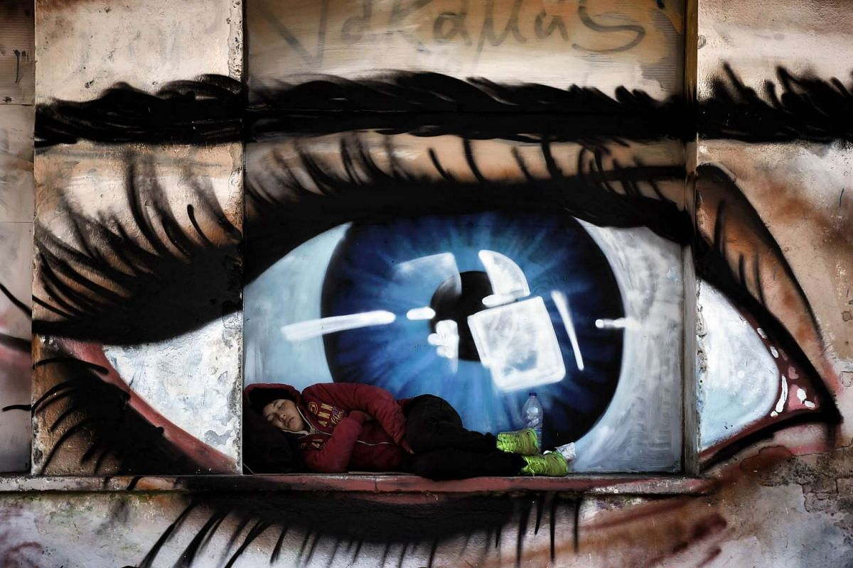 A migrant woman sleeping in front of graffiti illustrating an eye at the port of Mytilene on the Greek island of Lesbos, on Oct 6, 2015. Europe is grappling with its biggest migration challenge since World War II.