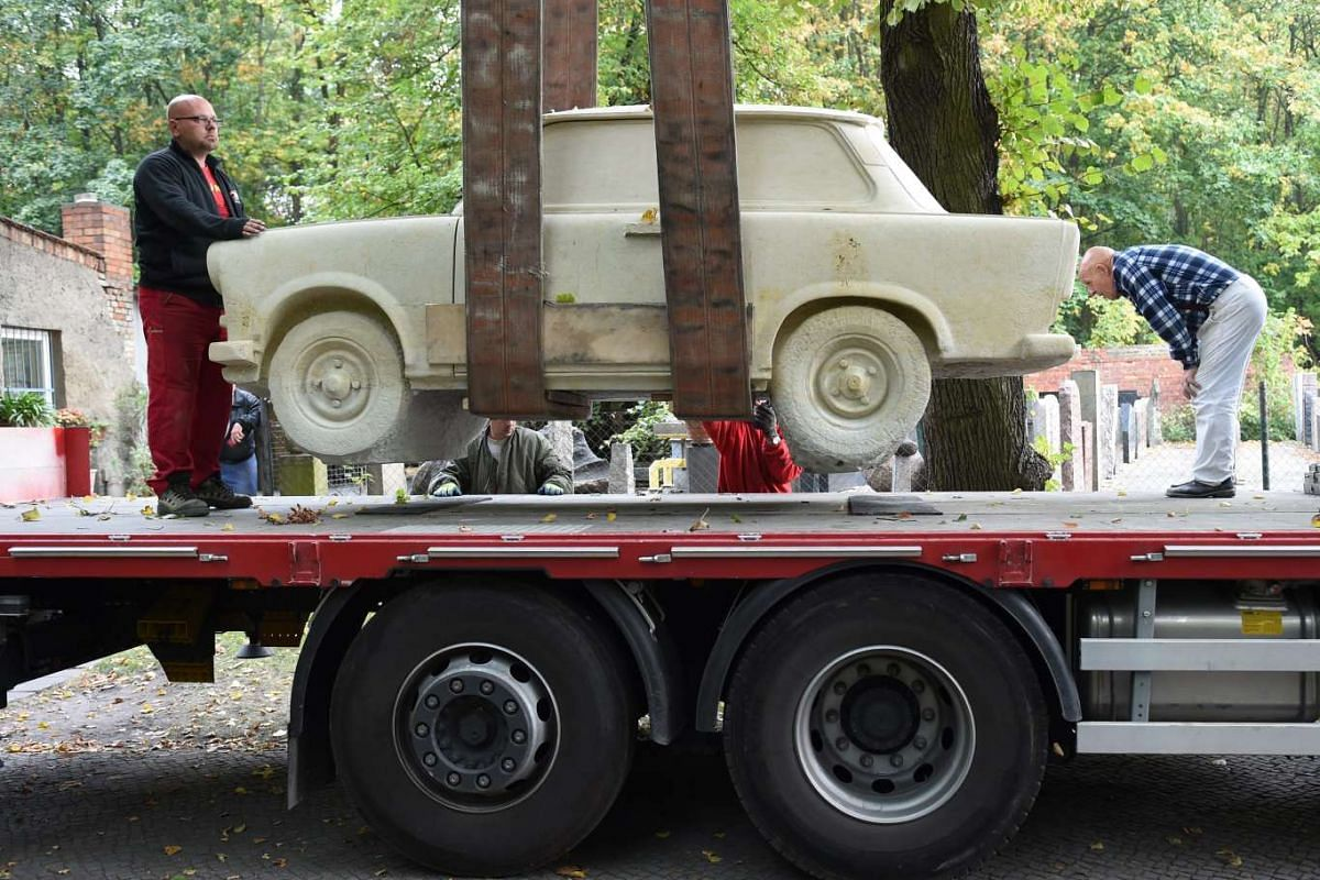 A Trabant 601 statue carved from a 25-tonne block of sandstone by sculptor Carlo Wloch is loaded onto a truck by a crane at a workshop in Berlin, Germany, on Oct 6, 2015. The 9-tonne artwork will be showcased at the vintage car fair Motorworld Classi