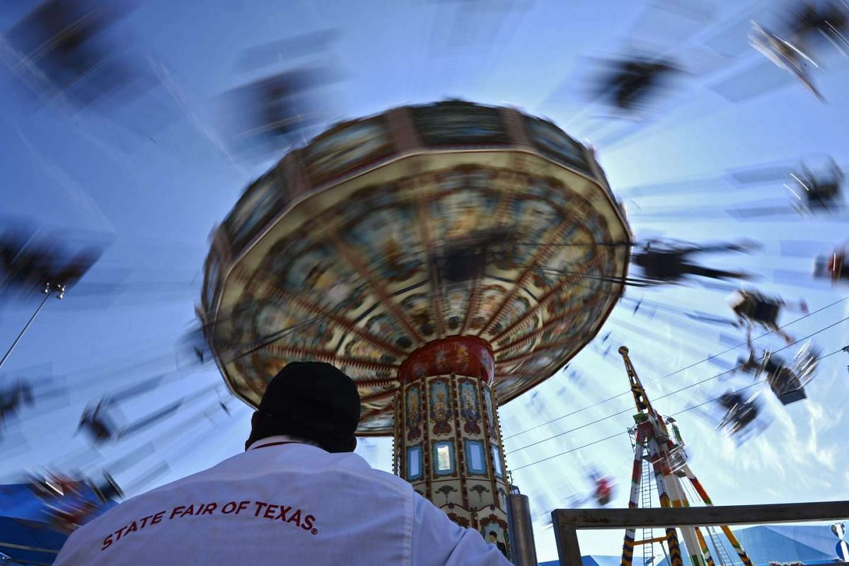 A worker watching people on the swing ride at the State Fair of Texas in Dallas, Texas, on Oct 6, 2015. The State Fair of Texas lasts for three weeks and draws thousands of spectators.
