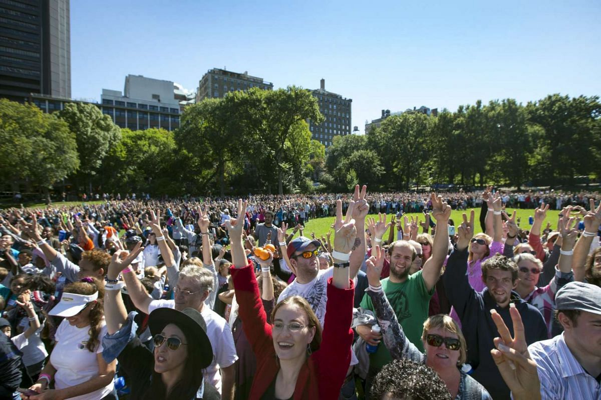 People flash the peace sign as they gather to form a giant peace symbol on the East Meadow of New York's Central Park, US, on Oct 6, 2015.