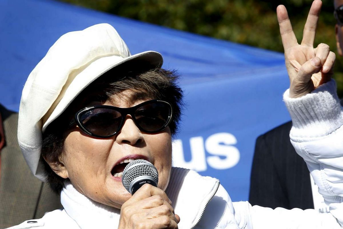 Yoko Ono shows the peace sign as she sings to thousands of people gathered to form a giant peace symbol on the East Meadow of New York's Central Park, US, on Oct 6, 2015.
