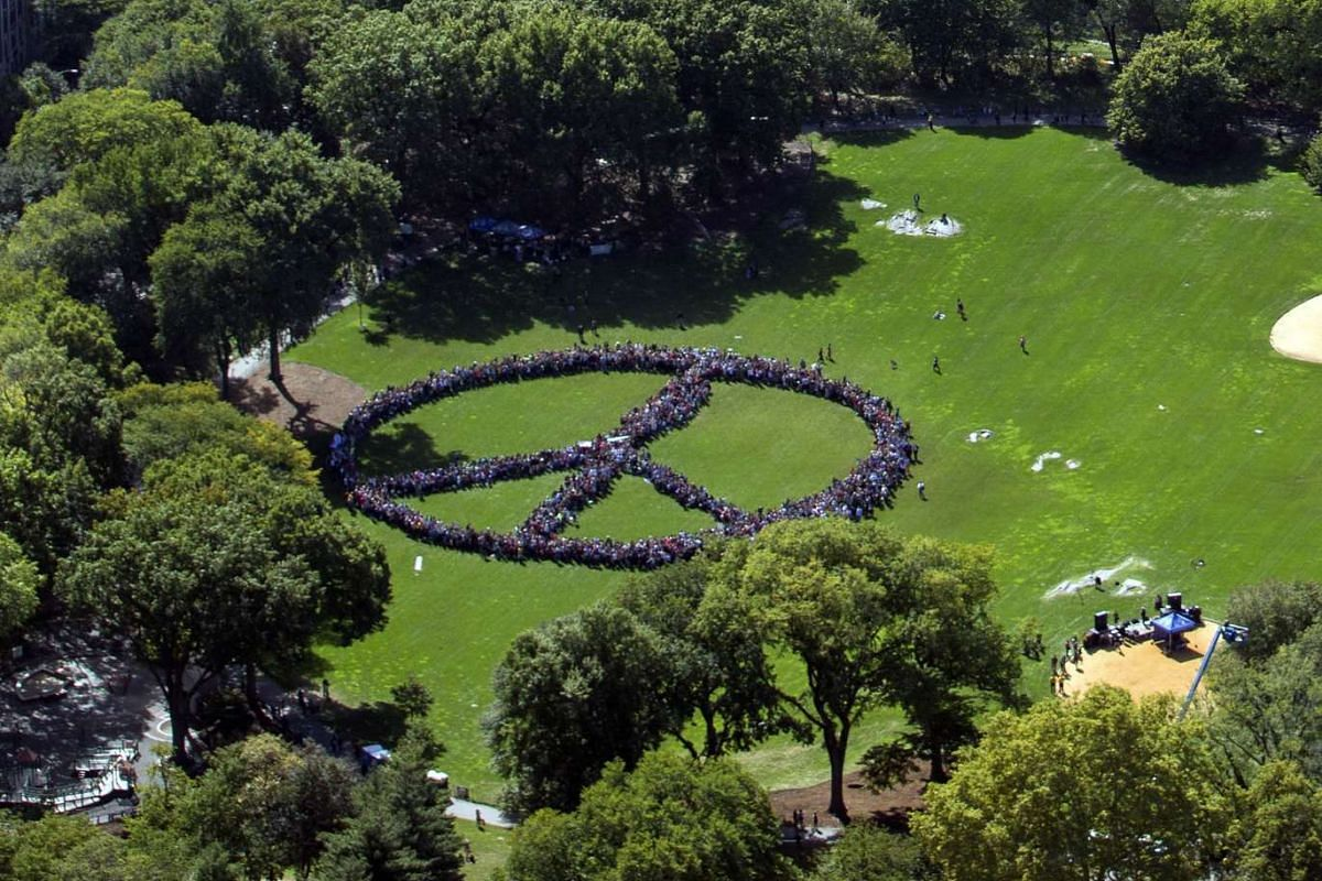 This handout photo provided by FlyNYON shows Yoko Ono and the John Lennon Educational Tour Bus brought thousands of people to come together and create a human peace sign in Central Park in New York, US, on Oct 6, 2015.