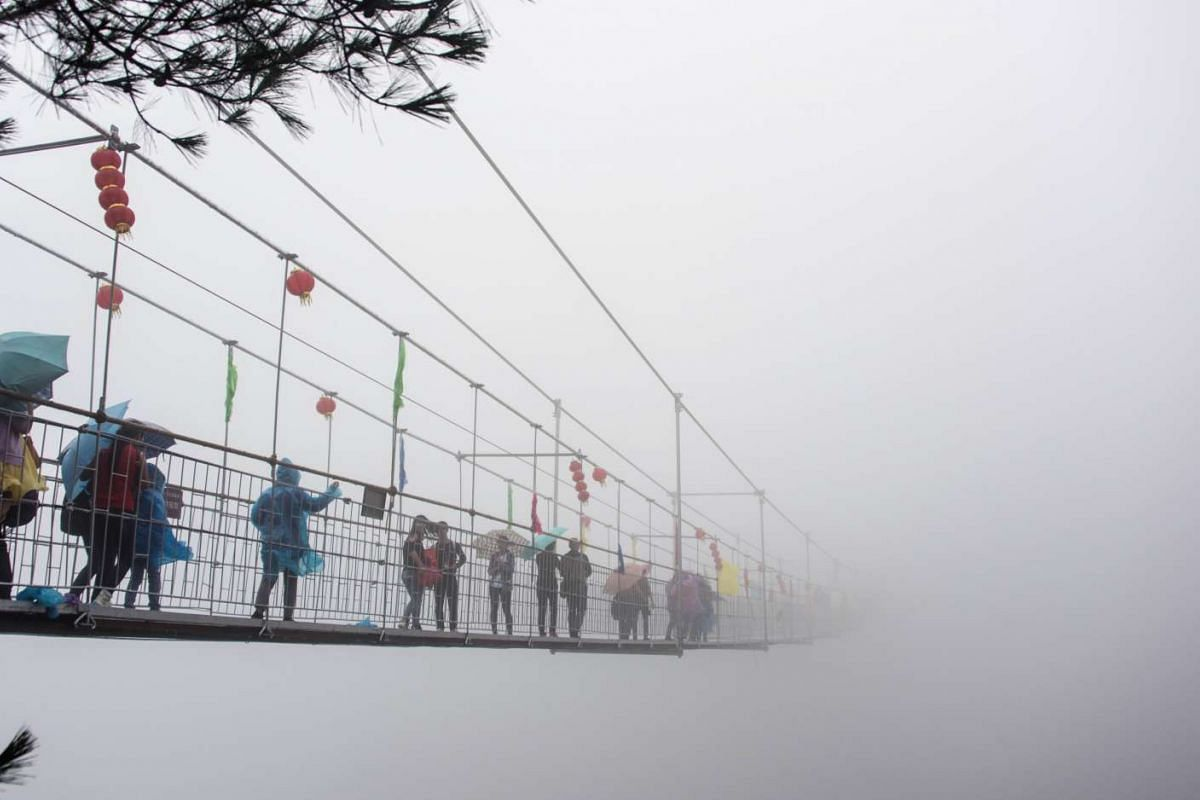 Chinese tourists walking across a glass-bottomed suspension bridge amid dense fog in the Shinuizhai mountains in Pingjang county, Hunan province, 150km from Changsha on Oct 6, 2015. The bridge, originally a wooden walkway spanning 300m across the 180